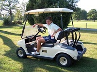 Golfer on a golf cart.
